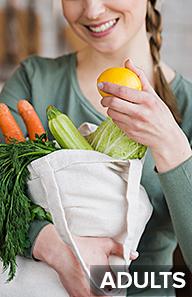 Woman holding bag of fresh vegetables