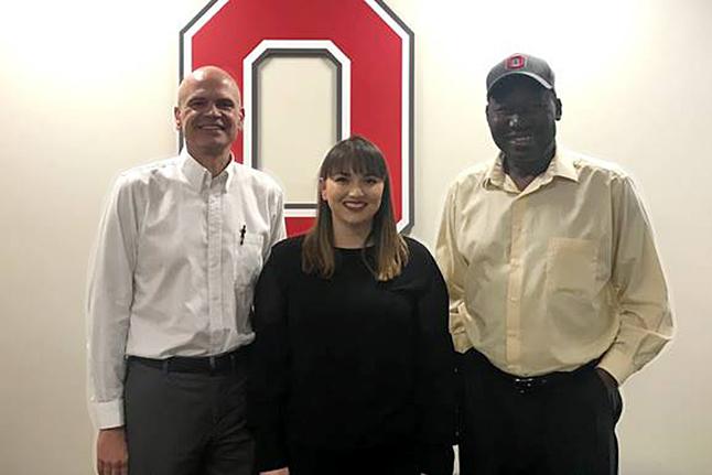 Katy Varney positing with committee members Schott Scheer and Robert Agunga