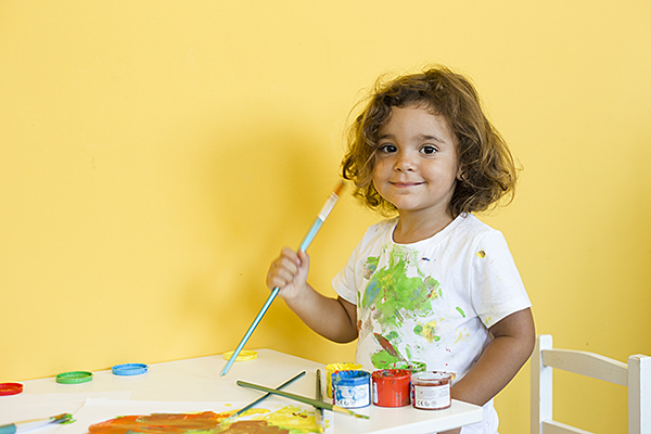 Young girl in art room holding paint brush
