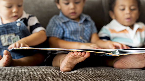 Three little boys on couch looking at book